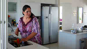 Adi Asulin stands in the kitchen of her family's remodeled apartment north of Tel Aviv. She saved thousands of dollars by flying to China to buy furnishings and flooring directly from manufacturers.
