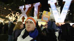 Super Bowl volunteer Ben Schreiber distributes fan guides for Super Bowl XLVI festivities in 2012.