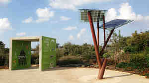 A small solar-powered tree, invented by Israeli energy entrepreneur Michael Lasry, stands at the edge of natural greenery.