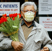 A man wears a protective mask as he carries a bouquet of flowers at Women's College Hospital in Toronto in March 2003, when SARS fears about were widespread.