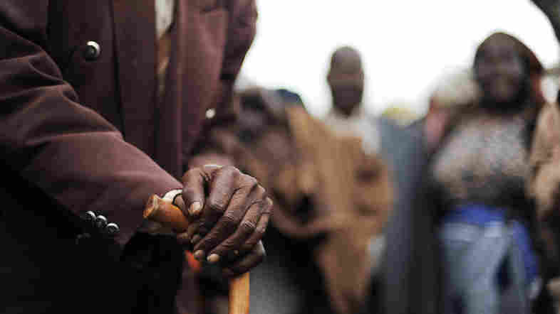 A Kenyan senior citizen leans on his cane. As people age in parts of Africa, they report declining levels of satisfaction with their life.