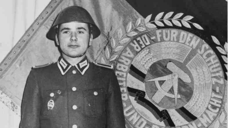 Harald Jaeger in uniform next to the flag of his East German border regiment in 1964.