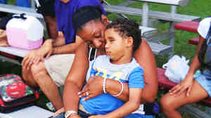 Five-year-old Kyle Romain sits on the lap of his grandmother, Barbara Romain, at a football game. Kyle lost his sight when he was hit by a stray bullet two months ago.