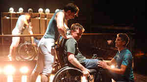 Young Mike (Joseph Carlson) antagonizes Mike (Michael Patrick Thornton) during a physical therapy session with Jerry (James Whalen).