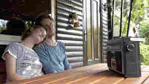 Germany, Hamburg, Man and woman listening to radio in cottage at allotment garden