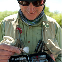 Photo of angler selecting a fly from box of flies.