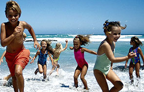 A group of kids playing at the beach.