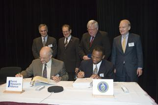 Fermilab Director Oddone and the Office of Science's Dennis Wilson sign the Fermilab M&O contract