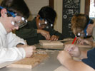Students carefuly cut the glider parts from balsam wood