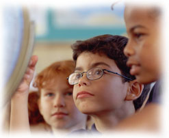 Photograph of three children looking at a globe in a classroom.