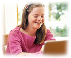 Photograph of a girl with Down's Syndrome using a laptop.