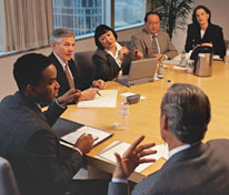 People in business outfit having a round table meeting.