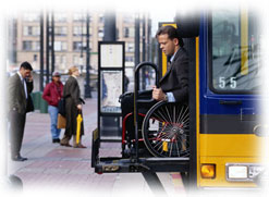 Photograph of a man in a wheel chair exiting a bus.