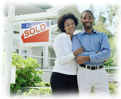 Photograph of a couple standing smiling next to a sold sign in front of a house.