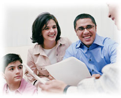 Photograph of a man looking over paperwork with a smiling couple and their son.