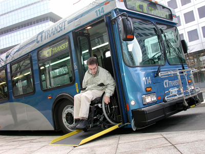 Rider manuevering wheelchair off of low-floor bus utilizing ramp.
