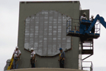 Workers install the radiating face of the phased array antenna during construction of the NWRT.