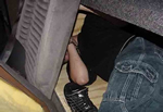 Image of a modified van used to smuggle illegal aliens and an illegal alien hiding underneath a seat with his shoes off