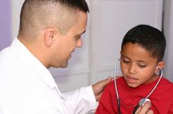 Doctor examining young boy.