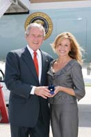 President George W. Bush presented the President's Volunteer Service Award to Sherri Goggin upon arrival in Marietta, Georgia, on Tuesday, July 22, 2008.  Goggin is the founder of Bundles of Joy, and a volunteer with Butterfly Dreams Farm Therapeutic Riding Program. To thank them for making a difference in the lives of others, President Bush honors a local volunteer when he travels throughout the United States.  He has met with more than 650 volunteers, like Goggin, since March 2002.