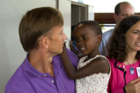 Ambassador Mark Dybul, PEPFAR Coordinator, is photographed with a child during a site visit to Reach-Out Mbuya Kinawataka Clinic on June 4, 2008.  This site visit coincided with the 2008 HIV/AIDS Implementers' Meeting. Photo by Arne Clausen.