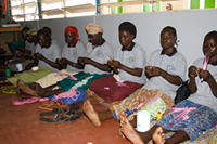 Participants in an income generating project at Reach-Out Mbuya Kinawataka Clinic create beadwork. Photo by Arne Clausen.