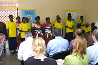 During a site visit to The AIDS Support Organization (TASO) on June 4, 2008, a group of people living with HIV/AIDS (PLWHA) perform a song about HIV treatment. Photo by Arne Clausen.