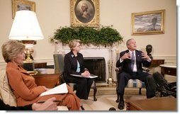 """President George W. Bush, seen with U.S. Secretary of Education Margaret Spellings, center, and Laura Bush, left, gestures as he speaks with reporters, Tuesday, Sept. 6, 2005 in the Oval Office at the White House, about efforts the Department of Education is undertaking with a program, """"Hurricane Help for Schools,"""" established to assist schools and students affected by Hurricane Katrina.  White House photo by Eric Draper"""