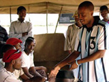 Zebras player Khumo 'Shoes' Motlhabane shakes hands with Pandamatenga locals before speaking to the crowd. The campaign encourages HIV testing for men and young people, two groups who are traditionally underrepresented at voluntary testing sites and government clinics.