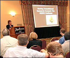 Conference speaker at the podium in front of a group of attendees