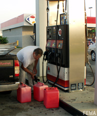 Photograph of a man filling gasoline containers at a gas station