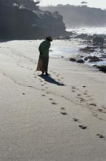 Photograph of a woman walking on a beach
