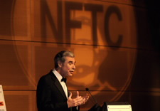 Gutierrez on podium with large NFTC logo in background. Click for larger image.