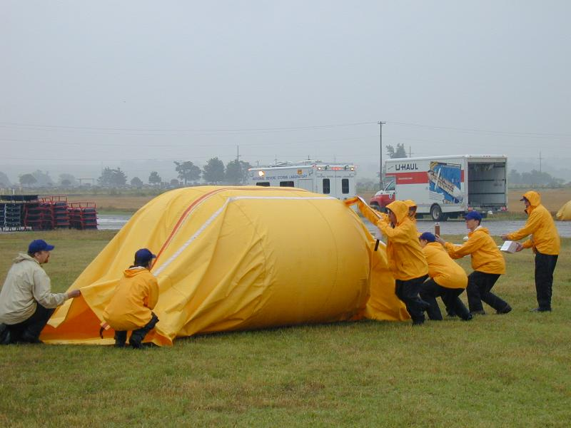 Students help scientists launch an instrumented balloon into a morning mesoscale convective system during TELEX 2003. The yellow tube is the launch tube containing the balloon, and crew members on the right are holding instruments in the balloon train.