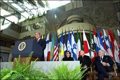 """""""Today, I call for a new compact for global development, defined by new accountability for both rich and poor nations alike,"""" states President George W. Bush in his address at the Inter-American Development Bank in Washington, D.C. March 14, 2002. Accompanying the President from left to right are: the lead singer of U2, Bono; Cardinal McCarrick and Worldbank President Jim Wolfensohn. White House photo by Tina Hager."""