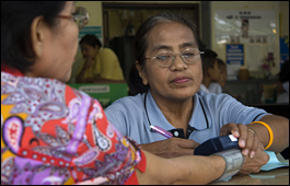 A health worker examining a woman's blood pressure at a primary health care centre in Thailand.