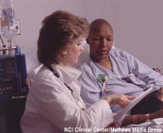 Photograph of a female health professional at the bedside of a bald female chemotherapy patient
