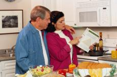 Photograph of a man and a woman reading a food label in the kitchen