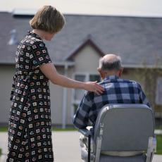 Photograph of a woman caring for a senior man in a scooter