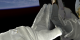 """This animation shows an astronauts gloved hand reaching out and touching the aft shroud area of the Hubble Space Telescope as if to say, """"Hello, old friend."""""""