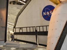 Technician watches clearance for space shuttle Endeavour's wing.