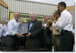 President George W. Bush holds the box after signing the Transportation Equity Act, with the help of Speaker of the House Dennis Hastert, R-Ill., at the Caterpillar facility in Montgomery, Ill., Wednesday, Aug. 10, 2005. Also pictured from left are Congressman Bill Thomas, R-Calif., Congressman Bobby Rush, D-Ill., and Senator Barack Obama, D-Ill. White House photo by Eric Draper
