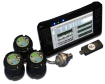 Photo showing a grouping of objects, including three sensors that are circular in shape and black in color with metal affixed to the top of each; a USB device; and a flat computer screen depicting measurements.