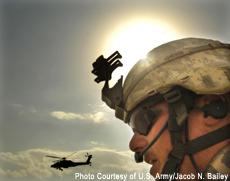 Fotografía de un soldado con un helicóptero en el fondo