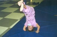 Photo of young girl with a below the elbow amputation (right arm), performing a headstand on a mat.