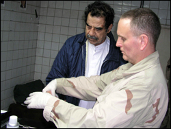 Image of Saddam Hussein being fingerprinted by an FBI agent