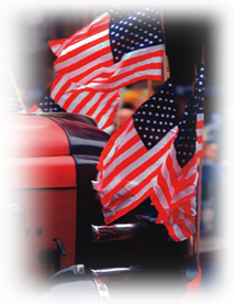 Image of a car with many US Flags waving