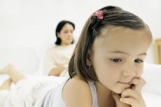 Fotografía de una niña con su mamá visible en segundo plano
