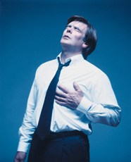 A photograph of a man clutching his chest