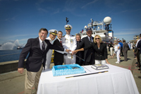 The ship's commissioning party ceremoniously cuts the first piece of commissioning cake.